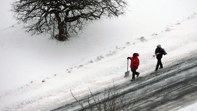 A couple of would-be snow shovelers walk along Rumsey Road in Yonkers after the overnight snowfall, Jan. 27, 2015.