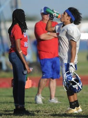 Cooper receiver Daelin Campos, right, hydrates during