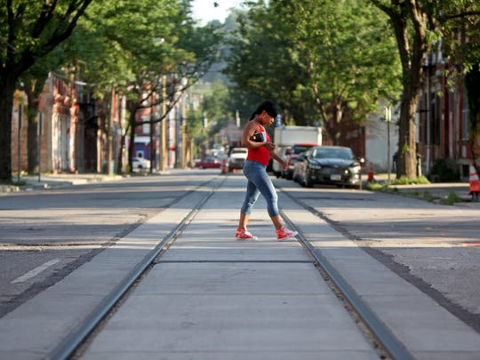 A young woman crosses the tracks along Race Street. When all the construction is finished, the city will repair the roads, from curb to curb.