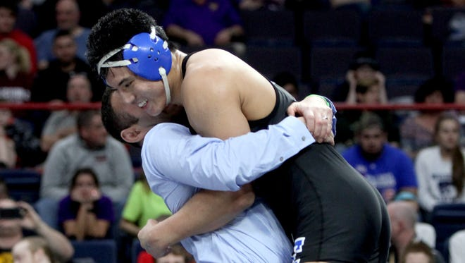 Cliffton Wang of Edgemont is hugged by coach Pete Jacobson after defeating Doug Simmons of Canestota in overtime to win the 182 pound championship at the finals of the NYSPHSAA Wrestling Championships at the Times-Union Arena in Albany Feb. 25, 2017.