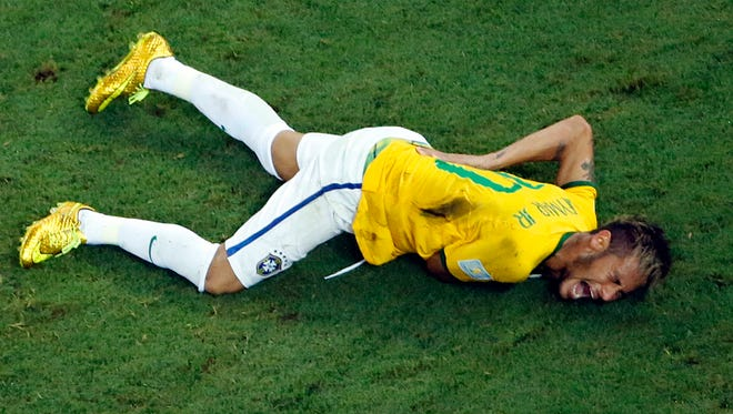 Brazil's Neymar grimaces in pain during the World Cup quarterfinal soccer match between Brazil and Colombia at the Arena Castelao in Fortaleza, Brazil, Friday, July 4, 2014. Brazil's team doctor says Neymar will miss the rest of the World Cup after breaking a vertebrae during the team's quarterfinal win over Colombia.