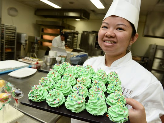 Pastry Chef Myra Tiamzon displays a platter of Christmas tree meringue cookies she prepared in the kitchen of Lotte Hotel Guam in Tumon on Monday, Dec. 21.