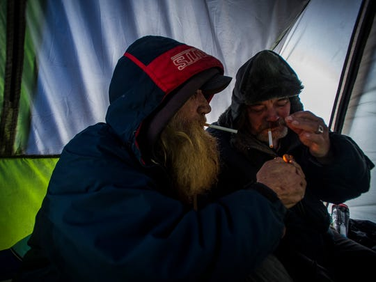 Lester Fielders and Don Abad have a smoke together, trying to warm up inside Fielders' tent near the interval in Burlington on Wednesday, Dec. 13, 2017. Several people live in the area, most saying that they can't find a bed in a shelter. Most here are veteran homeless and say they know all too well how to survive when temps dip into the single digits or worse.