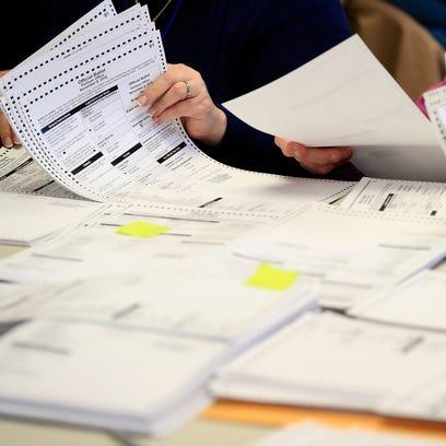 Workers sort through ballots on Thursday, December