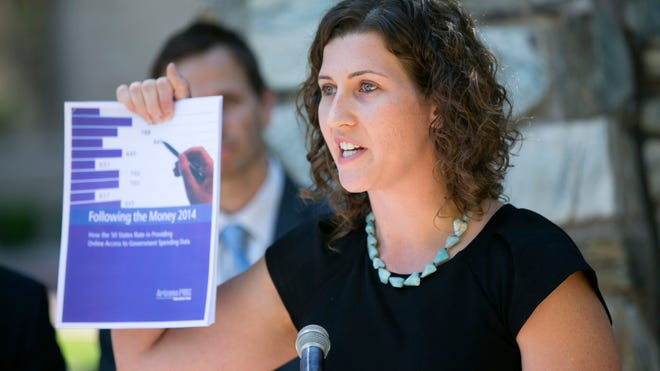Serena Unrein of Public Interest Research Group's Arizona chapter holds up PIRG's transparency report Tuesday while announcing that Arizona had received a B from the group.