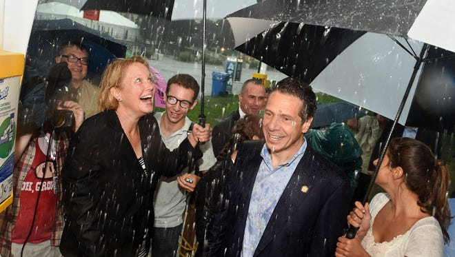 Gov. Andrew Cuomo huddles under umbrellas Thursday, Aug. 21, 2014. with Onondaga County Executive Joanie Mahoney, left, and his daughter Michaela, as they visit the New York State Fair on the opening day in Geddes, N.Y.