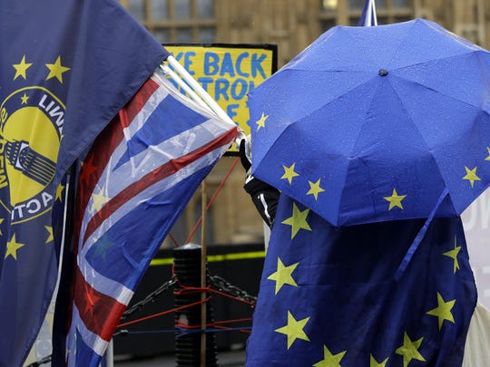 An anti-Brexit demonstrator shelters under an umbrella in the pattern of the European Union flag outside parliament in London, Jan. 24, 2019.