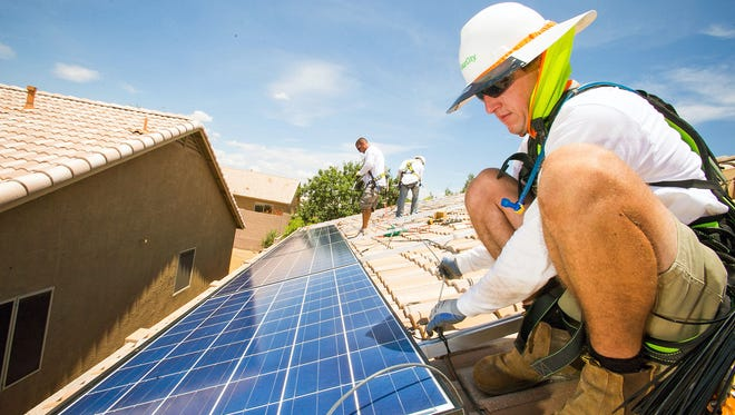 A solar installer works on a panel atop a home in Cave Creek.