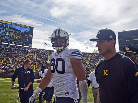 BYU defensive lineman Bronson Kaufusi (90) talks with Michigan head coach Jim Harbaugh after the game in Ann Arbor, Mich., on Saturday. Michigan won 31-0.