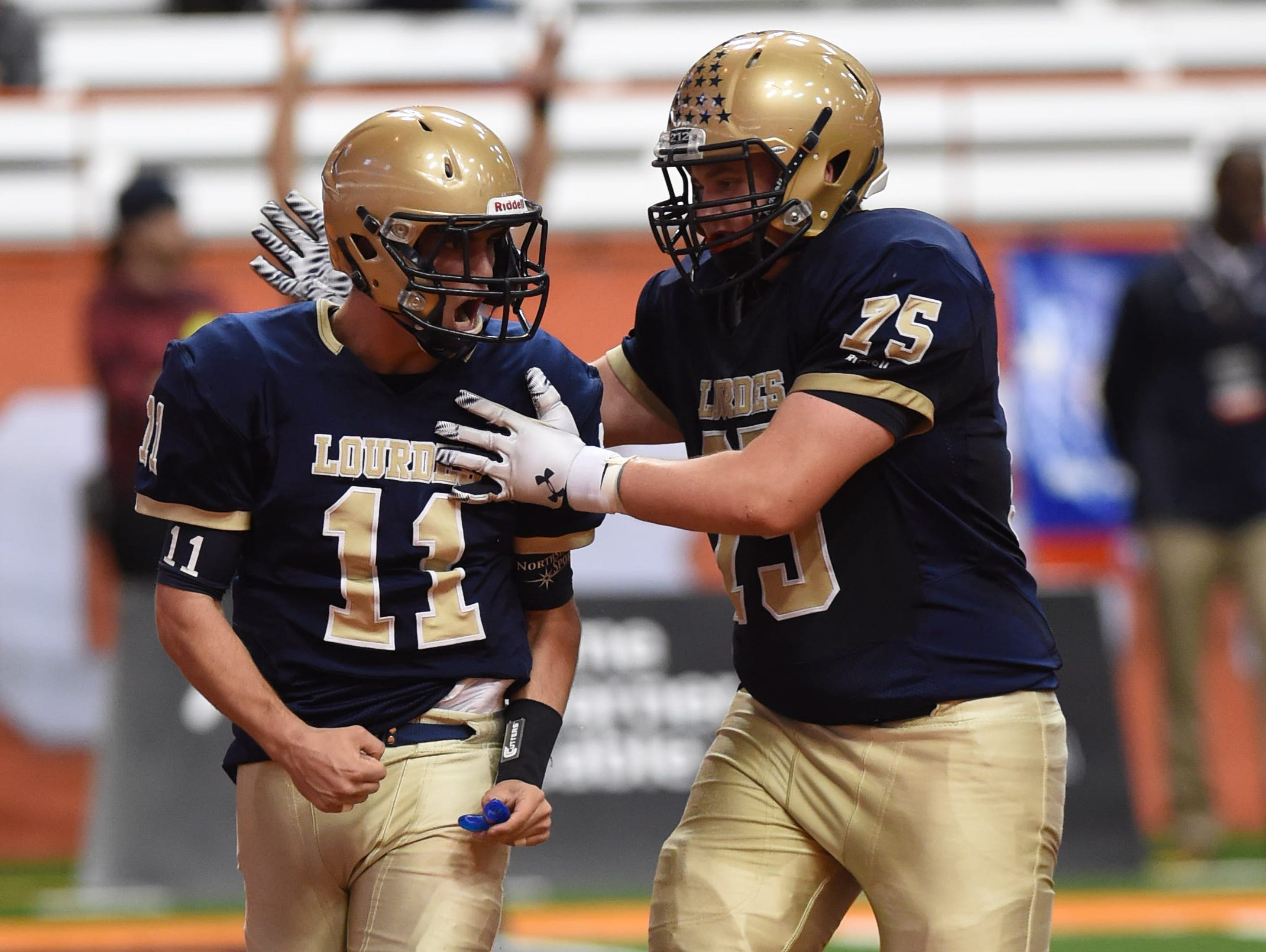 Lourdes' Dean Rotger and Liam Hilderbrand celebrate a touchdown during the New York State Championship final versus South Park in Syracuse on Friday.