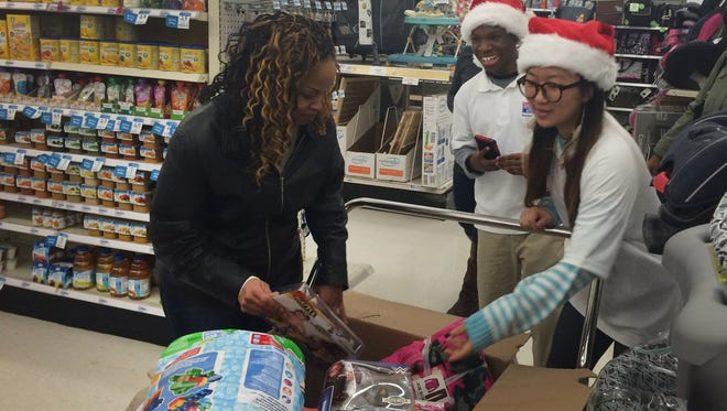 Karlisa Ducan gets help with her gifts from University of Detroit Mercy students at Kmart on E. 10 Mile in Warren