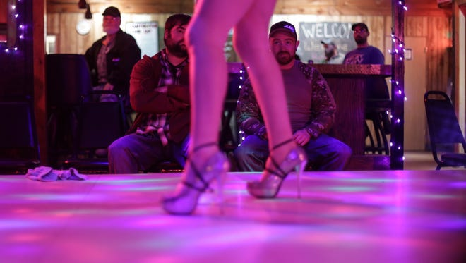 John Dunn of Marquette and Kory Luke of Gwinn watch as Ariel dances on stage on Saturday November 14, 2015 at Big Bon's in Rock at the Upper Peninsula's only strip club.