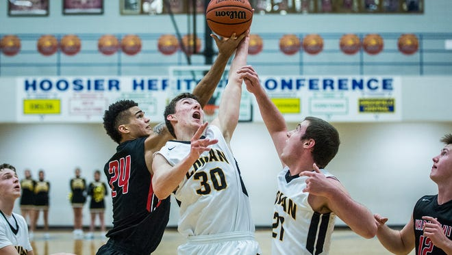 Wapahani's Jarod Hundley fights for a rebound past Cowan's Michael Smith during their game at Delta High School Thursday, Jan. 14, 2016.