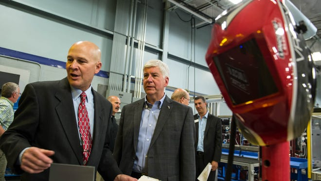 Kellogg Community College Regional Manufacturing Technology Center Director Tom Longman shows Gov. Rick Snyder some of the training technology during a tour on Thursday.