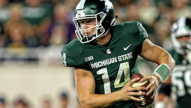 Michigan State Spartans quarterback Brian Lewerke (14) scrambles with the ball during the first half a game against the Notre Dame Fighting Irish at Spartan Stadium.
