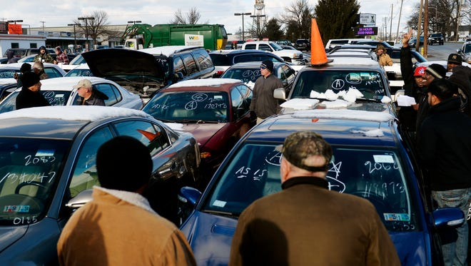 Prospective buyers gather around a vehicle up for sale at the York County Drug Task Force auction at Schaad Detective Agency in November of 2014.