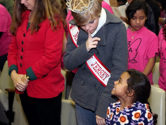 Miss New Jersey Junior Teen Shellby Watts, 15, of Vineland, hushes 4-year-old Raelyn Camarillo of Philadelphia, during the invocation at the Vineland tree lighting ceremony on Sunday.
