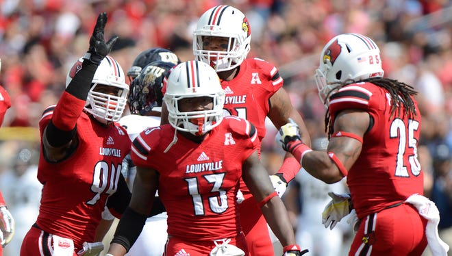 Louisville Cardinals defensive end Lorenzo Mauldin (94) and safety Calvin Pryor (25) celebrate the 3rd down stop of linebacker James Burgess (13) against the FIU Golden Panthers during the first quarter of play at Papa John'sCardinal Stadium.