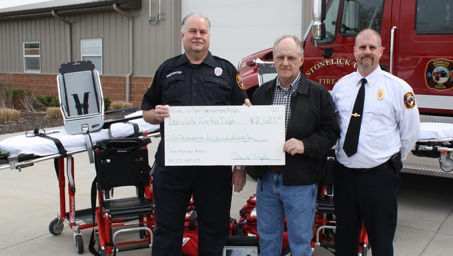 Firefighter Dave Knapke (left) presents a check for $2,621 from the Stonelick Township Firefighters Association to Stonelick Township Trustee John Hanley. The check helped pay for some emergency medical gear, shown in rear, purchased by the department.