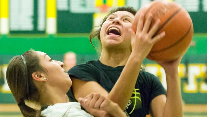 Mayfield High School's Brenda Prieto, right, goes up for a shot as Jazmine Rios takes the charge on Monday morning at Mayfield High School during the first official day of high school basketball practice in New Mexico.