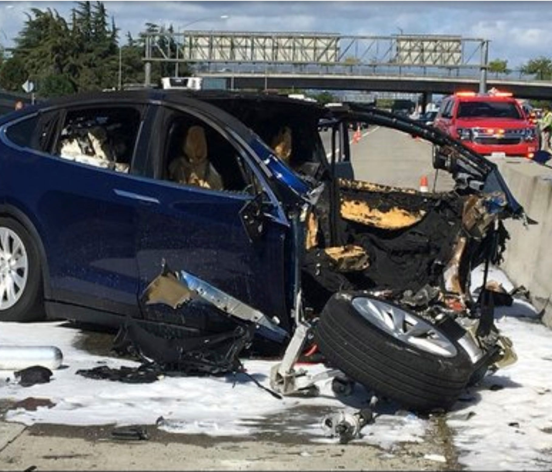 In this Friday March 23, 2018 photo provided by KTVU, emergency personnel work a the scene where a Tesla electric SUV crashed into a barrier on U.S. Highway 101 in Mountain View, Calif. The National Transportation Safety Board has sent two investigat