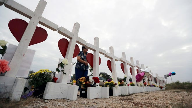 A woman visits a makeshift memorial along the highway for the victims of the church shooting at Sutherland Springs Baptist Church, in Sutherland Springs, TX.