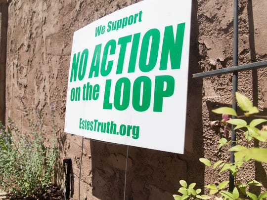 Residents display signs against the loop proposed for