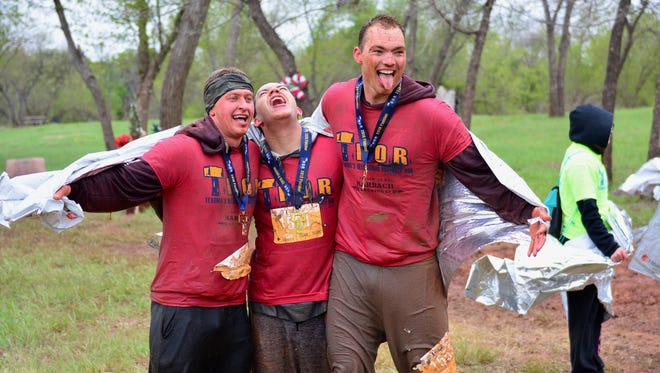 In this file photo, a medaled trio celebrate the successful T.H.O.R. completion of their muddy adventure.