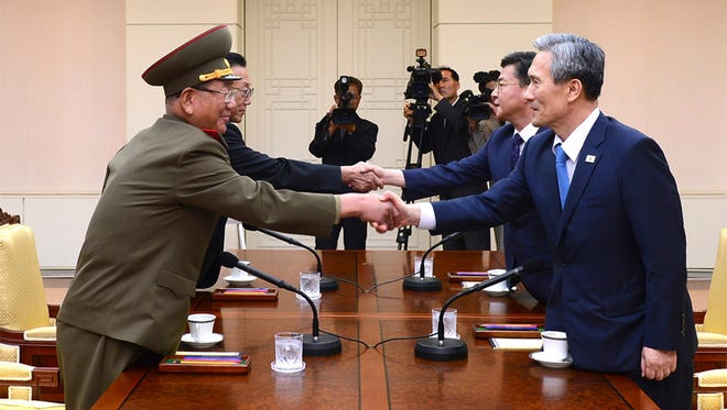 In this Aug. 22, 2015, file photo South Korean National Security Director, Kim Kwan Jin, right, and Unification Minister Hong Yong Pyo, second from right, shake hands with Hwang Pyong So, left, North Korea' top political officer for the Korean People's Army, and Kim Yang Gon, a senior North Korean official responsible for South Korean affairs, during their meeting at the border village of Panmunjom in Paju, South Korea.