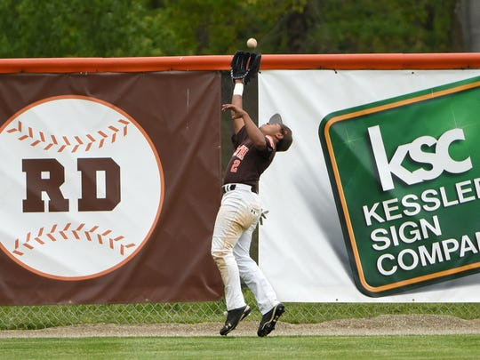Heath outfielder Adryn McCoy makes a catch near the fence for the out against Licking Valley. The Bulldogs defeated Panthers 4-1 and advance to the second round of D-II district baseball tourney.