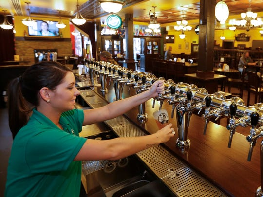 Brianna Grantier pours a beer from a tap at The Celtic Cowboy.