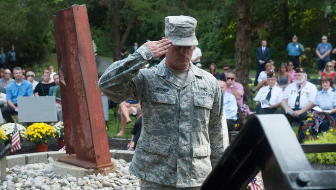 Senior Airman David Heitman salutes during the Patriot Day Memorial Ceremony at Chestnut Branch Park in Mantua Twp. Thursday, September 11, 2014.