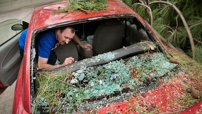 Russell Edwards looks through his damaged car, Thursday, July 24, 2014, in north Spokane, Wash. Edwards narrowly escaped injury on Wednesday afternoon when a tree crashed onto his 1998 Ford Mustang as he sat in the driver's seat in his driveway. (AP Photo/The Spokesman-Review, Dan Pelle)