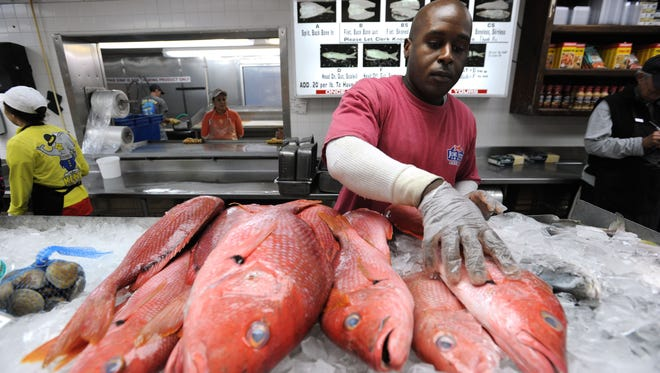 """Joe Patti's Seafood employee Terrance Williams stocks a display cooler with red snapper. The iconic fish market was named to the """"Taste 50"""" by Taste of the South magazine."""