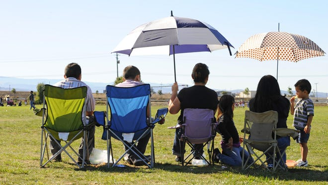 Families deal with unseasonably hot weather by bringing their own shade as they watch the youth leagues compete in November 2012 at the Constitution Soccer Complex in Salinas.
