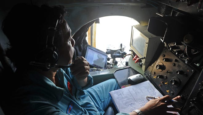 A Vietnamese Air Force crew member looks out the window during search operations for the missing Malaysia Airlines flight MH370 on Sunday.