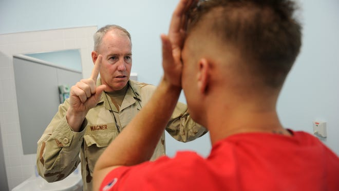 U.S. Navy Capt. Michael Wagner, MD, a neurologist and Traumatic Brain Injury Director at the Kandahar Air Field Role 3 Medical Treatment Facility, examines a soldier after he was exposed to an IED blast, in 2010.