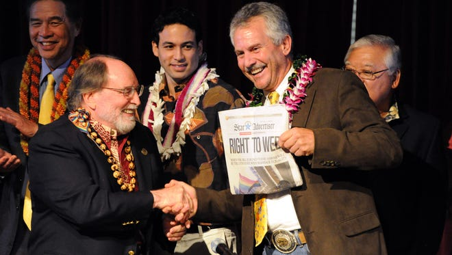 Gov. Neil Abercrombie, left, and former Sen. Avery Chumley hold up a copy of the Star Advertiser after Abercrombie signed the bill legalizing gay marriage in Hawaii on Nov. 13, 2013 in Honolulu.
