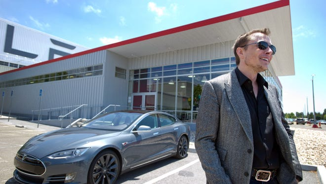 CEO Elon Musk with a new Model S  car outside the Tesla customer deliver area at the Tesla Fremont, Calif., factory