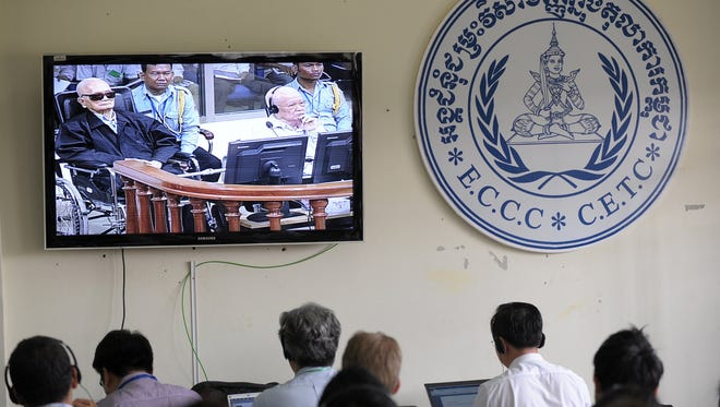 """Cambodian and international journalists watch a live video feed showing former Khmer Rouge leader """"Brother Number Two"""" Nuon Chea, and former Khmer Rouge head of state Khieu Samphan in the courtroom during their trial on Thursday."""