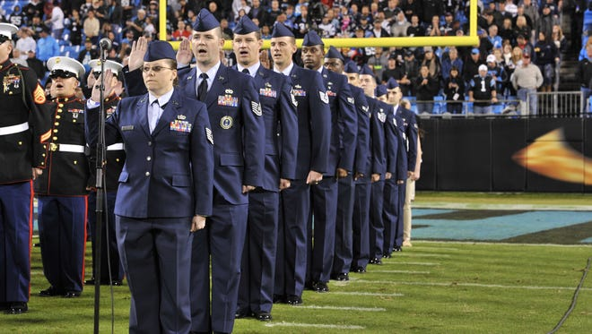 Airmen participate in a re-enlistment ceremony before the start of the Carolina Panthers and New England Patriots game at Bank of America Stadium in Charlotte in November 2013.