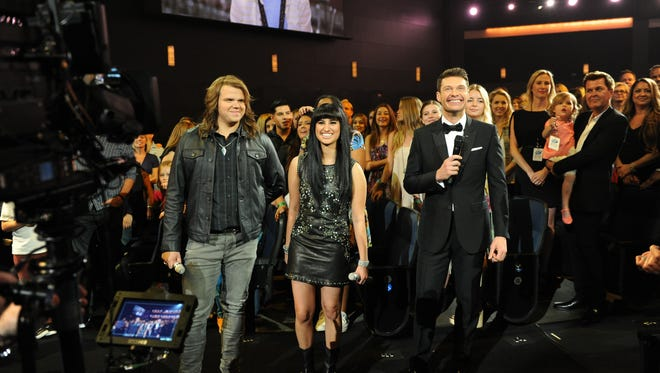 """American Idol XIII"" finalists Jena Irene and Caleb Johnson and Host Ryan Seacrest during the ""American Idol"" finale at the Nokia Theatre on Wednesday, May 21, in Los Angeles, Calif."