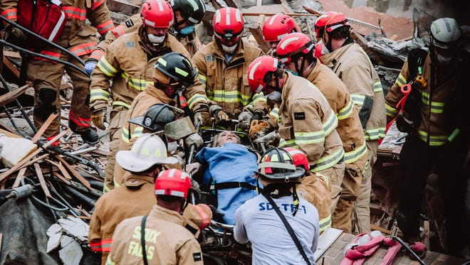 Firefighters rescue a woman from a collapsed building on Friday in downtown Sioux Falls. The woman, identified as Emily Fodness, had been trapped for three hours.