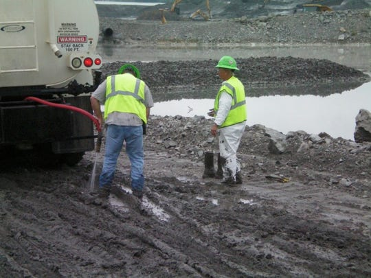 This photo depicts workers with no protective gear mired in coal ash while cleaning it off a vehicle leaving the site.
