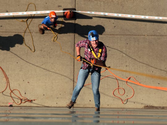 Reporter Michael Izzo rappels down a 10-story building at One Garret Mountain Plaza as part of a charity event to raise money for local Girl Scouts.  September 18, 2015, Woodland Park, NJ.