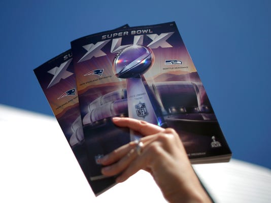 A vendor offers programs to the fans outside of the stadium ahead of the the NFL Super Bowl XLIX football game between the Seattle Seahawks and the New England Patriots in Glendale