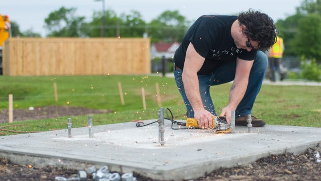 Professor and artist Steven Durow installs a sculpture at Rivers Edge Apartments on Thursday morning.