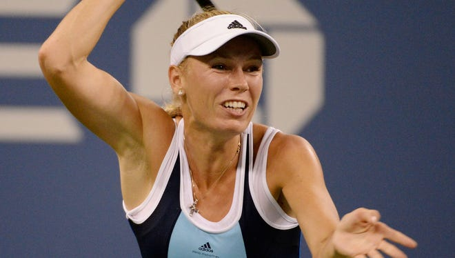 Caroline Wozniacki returns a shot to Chanelle Scheepers on Day 4 of the 2013 US Open at the Billie Jean King National Tennis Center.