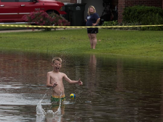 Karter Micklos plays in a flooded street in the Thousand