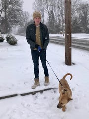 Zach Barkley, an Oakland High sophomore, takes Pippa for a first walk in snow down East Main Street.